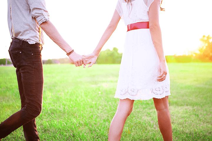 手を繋いで歩く若い男女