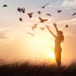 空に飛ぶ鳥を仰ぐ女性
