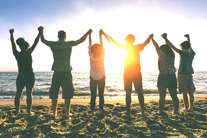 砂浜で太陽に向かって繋いだ手を上げる若者たち