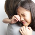 泣いている娘を抱く母親
