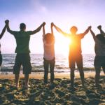 浜辺で手を繋ぐ若者たち