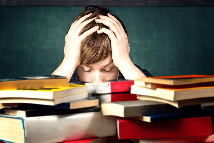 たくさんの本に頭を抱える子ども