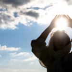 太陽の光に手をあげる女性