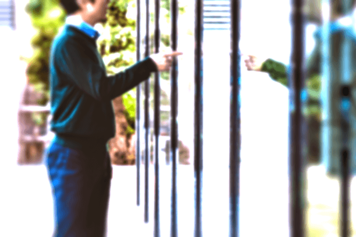 ガラスに映った自分を指差す男性