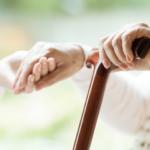 老人の手を握る女性